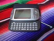 ENG06BB02 Handheld T Mobile cell phone computer with pointer and keyboard on Latin American blanket; IT, hi-tech. England.