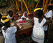 TNZ93DC1059 Costumed children play-act wedding, eat hungrily: feast of rice, corn, cooked banana; Ifakara, Morogoro Rgn, S.Tanzania.
